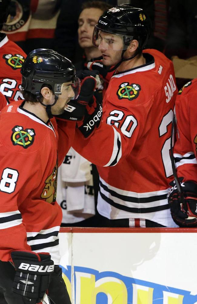 Chicago Blackhawks' Nick Leddy (8) slaps gloves with teammates after scoring a goal during the first period of an NHL preseason hockey game against the Washington Capitals in Chicago, Saturday, Sept. 28, 2013