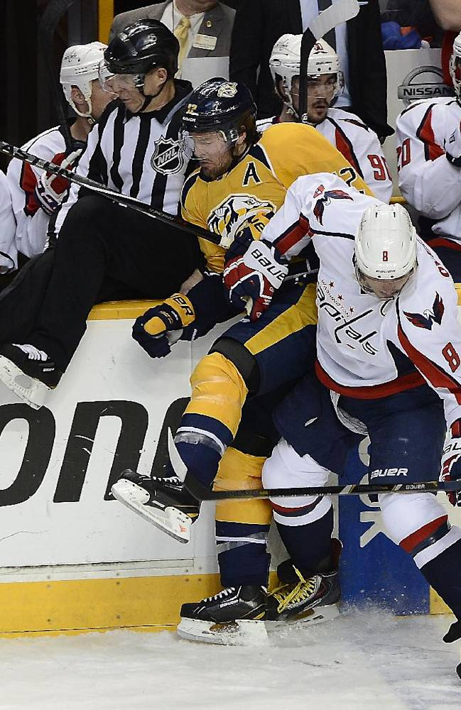 Washington Capitals right wing Alex Ovechkin (8), of Russia, checks Nashville Predators forward Mike Fisher (12) into the boards as linesman Brad Lazarowich, left, tries to get out of the way in the second period of an NHL hockey game on Sunday, March 30, 2014, in Nashville, Tenn
