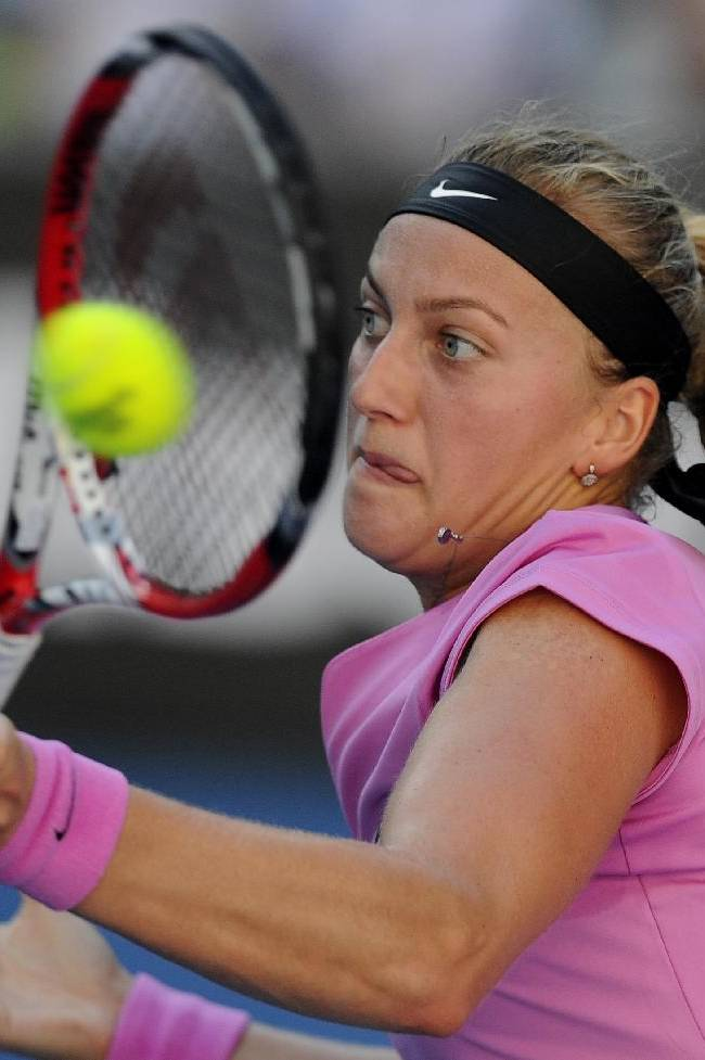 Petra Kvitova of the Czech Republic makes a backhand return to Luksika Kumkhum of Thailand during their first round match at the Australian Open tennis championship in Melbourne, Australia, Monday, Jan. 13, 2014