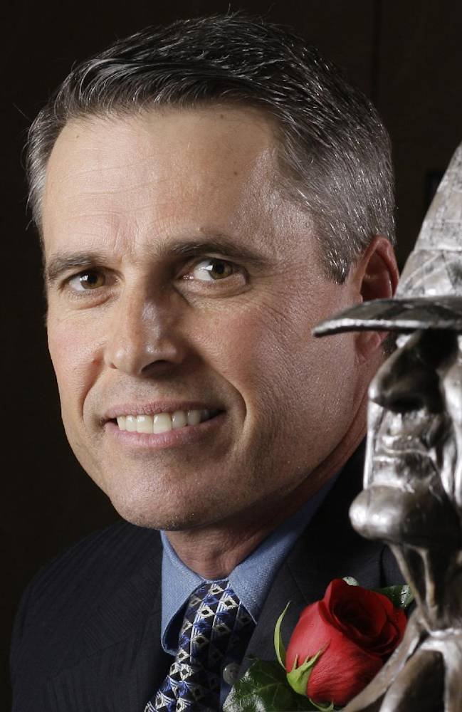 In this Jan. 14, 2010 file photo, NCAA college football coach Chris Petersen, of Boise State, poses with the Bear Bryant trophy in Houston. A person familiar with the decision tells The Associated Press that Petersen has agreed to leave Boise State and be the football coach at Washington. The person told spoke on the condition of anonymity Friday morning, Dec. 6, 2013,  because the hiring had not been announced by Washington