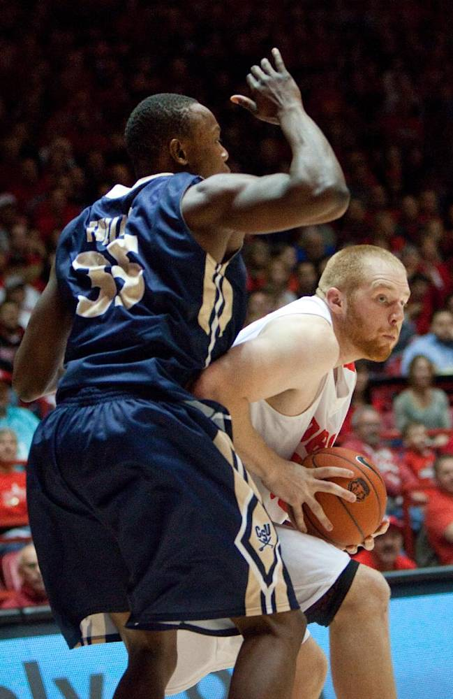 New Mexico's Alex Kirk, right, tries to score around Charleston Southern's Alhaji Fullah in the second half of an NCAA college basketball game Sunday, Nov. 17, 2013, in Albuquerque, N.M