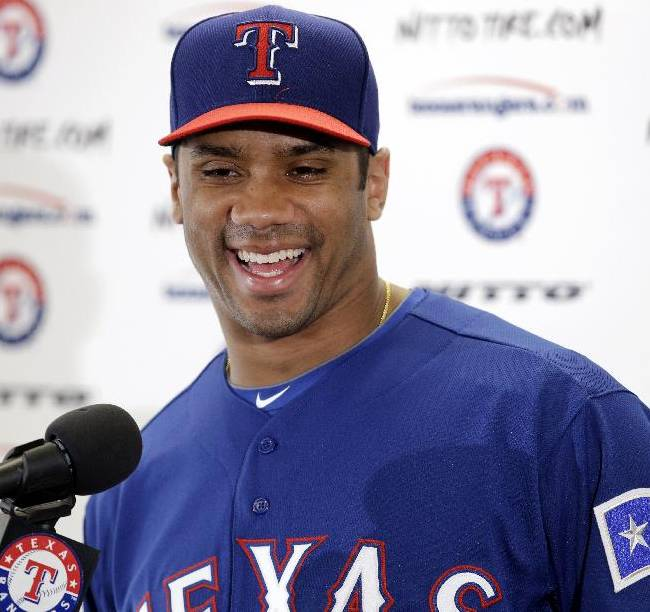 Seattle Seahawks quarterback Russell Wilson responds to a question during a news conference after a full day's workout with the Texas Rangers during spring training baseball practice, Monday, March 3, 2014, in Surprise, Ariz