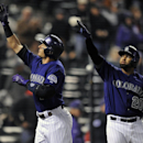 Colorado Rockies Troy Tulowitzki, left, and Wilin Rosario, right, celebrate a home run by Tulowitzki in the sixth inning of the MLB baseball game against the Chicago White Sox on Monday, April 7, 2014, in Denver. The Rockies won 8-1 The Associated Press