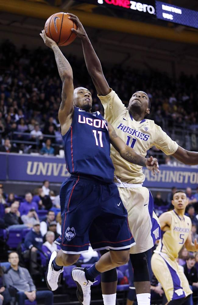 Connecticut's Ryan Boatright, left, has a shot blocked by Washington's Mike Anderson in the second half of an NCAA college basketball game in Seattle on Sunday, Dec. 22, 2013. UConn won 82-70