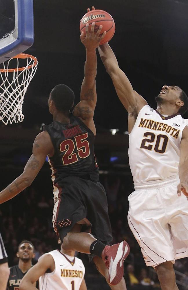 Minnesota's Austin Hollins (20) blocks the shot of Florida State's Aaron Thomas (25) during the second half of an NCAA college basketball game in the semifinals of the NIT on Tuesday, April 1, 2014, in New York. Minnesota won 67-64