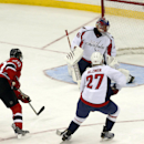 New Jersey Devils center Ryan Carter, left, scores a goal on Washington Capitals goalie Jaroslav Halak, top, of Slovakia, as defenseman Karl Alzner (27) watches during the third period of an NHL hockey game, Friday, April 4, 2014, in Newark, N.J. The Devi