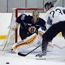 Boston Bruins goalie Tuukka Rask watches the puck get away from center Chris Kelly (23) during hockey training camp in Wilmington, Mass., Friday, Sept. 19, 2014 The Associated Press