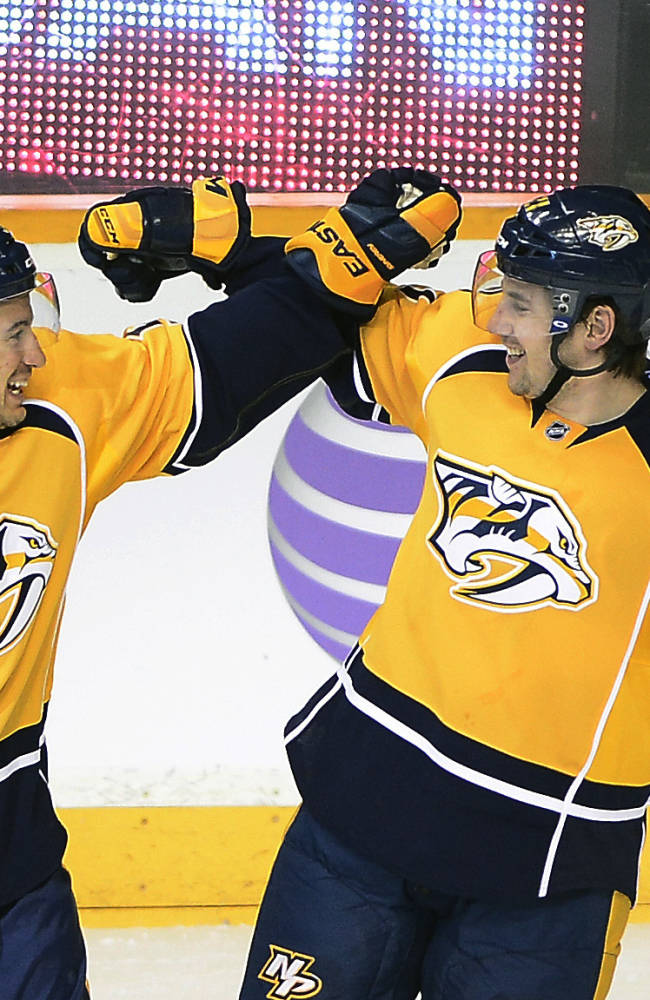 Nashville Predators defenseman Michael Del Zotto, left, celebrates with Simon Moser (5), of Switzerland, after Moser scored a goal in the third period of an NHL hockey game against the Winnipeg Jets on Saturday, March 1, 2014, in Nashville, Tenn