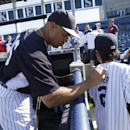 New York Yankees' Carlos Beltran autographs the jersey of 10-year-old Asher Heldond before the Yankees' spring exhibition baseball game against the Philadelphia Phillies in Tampa, Fla., Tuesday, March 25, 2014 The Associated Press