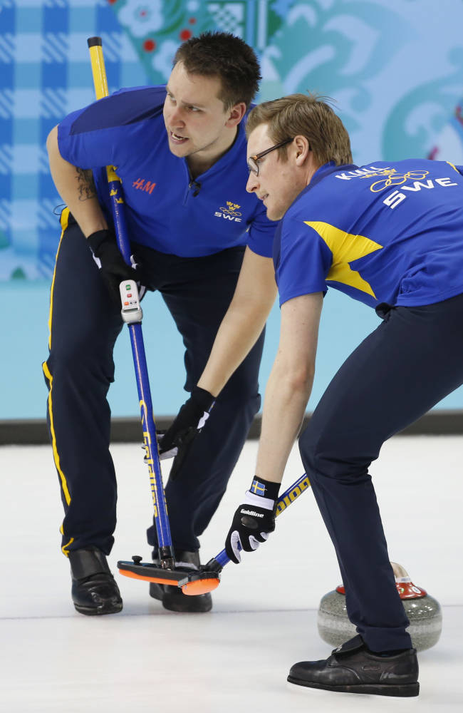 Sweden's Fredrik Lindberg, left, and Viktor Kjaell sweep during men's curling competition against Germany at the 2014 Winter Olympics, Saturday, Feb. 15, 2014, in Sochi, Russia