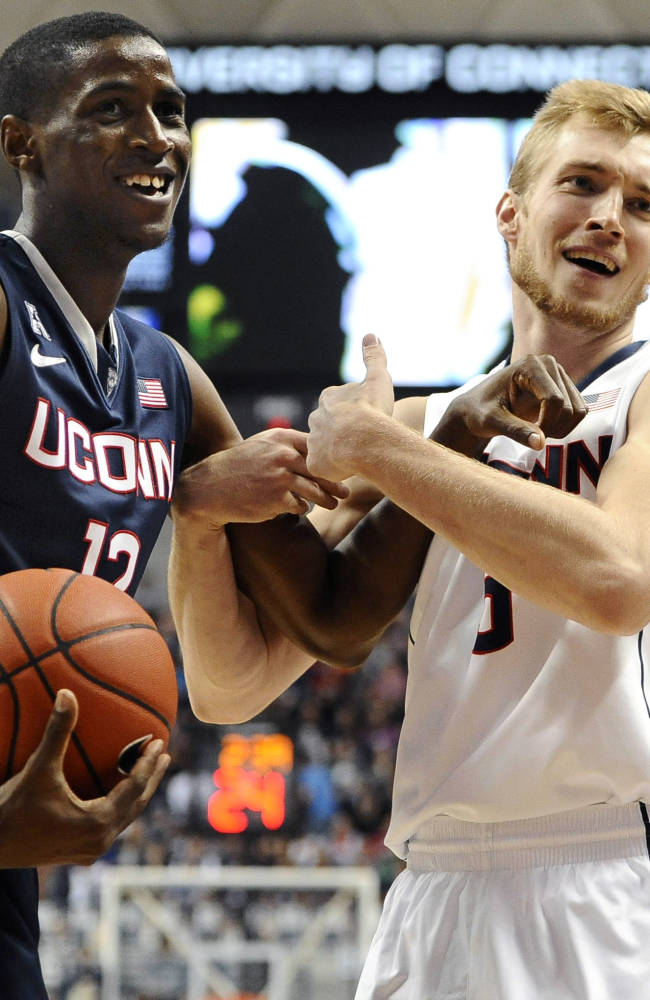 In this Oct. 18, 2013, file photo, Connecticut's Kentan Facey, left, and Niels Giffey smile as they look to an official for a call during an intrasquad scrimmage in Storrs, Conn. Facey was granted a waiver to play this season and allowed four years of eligibility by the NCAA, which was looking into eligibility issues related to his schooling in Jamaica, the university said Friday