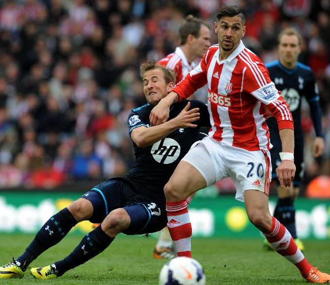 Tottenham's Harry Kane, left, clashes Stoke's Geoff Cameron during the English Premier League soccer match between Stoke City and Tottenham Hotspur at the Britannia Stadium in Stoke On Trent, England, Saturday, April 26, 2014