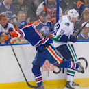 Vancouver Canucks' Alexander Edler (23) dodges a hit from Edmonton Oilers Jordan Eberle (14) during the second period of an NHL hockey game Saturday, Nov. 1, 2014, in Edmonton, Alberta The Associated Press