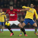 Manchester United s Robin van Persie, left, fights for the ball against Arsenal s Mikel Arteta during their English Premier League soccer match at Old Trafford Stadium, Manchester, England, Saturday Nov. 10, 2013