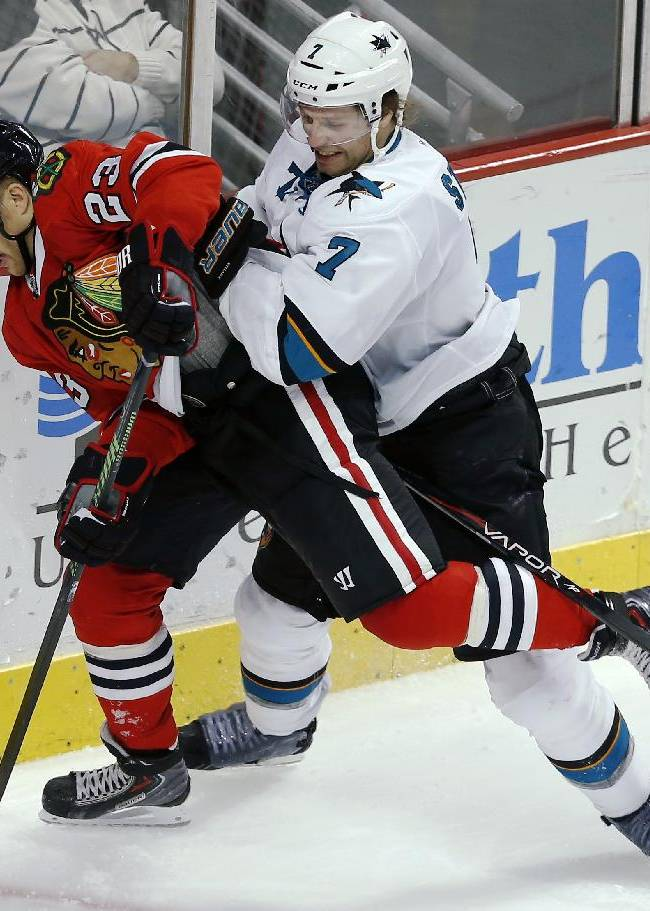 Chicago Blackhawks right wing Kris Versteeg (23) and San Jose Sharks defenseman Brad Stuart (7) battle for the puck during the third period of an NHL hockey game on Sunday, Nov. 17, 2013, in Chicago