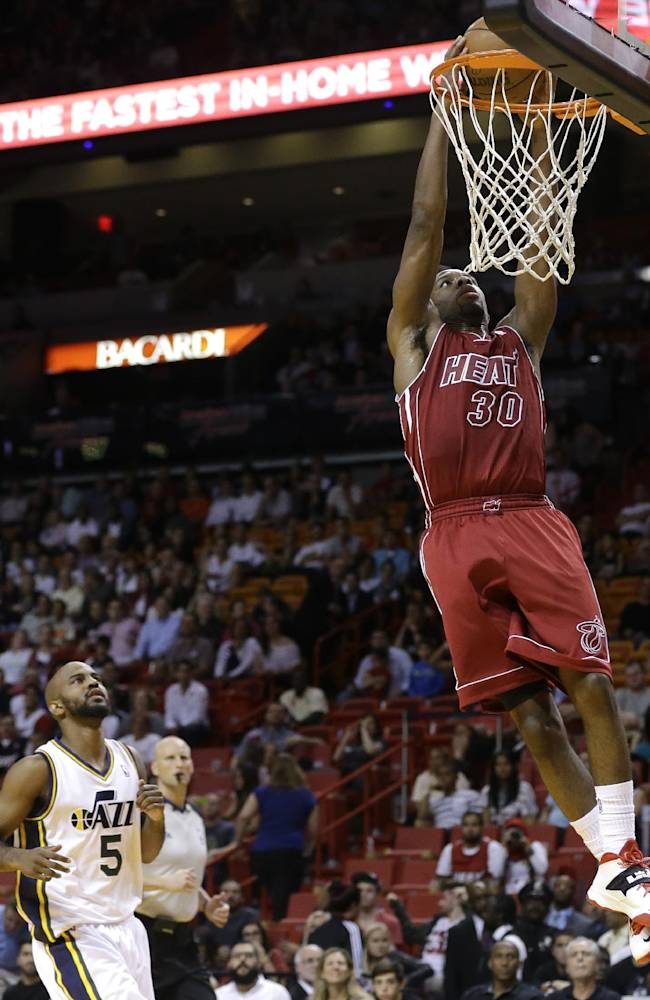 Miami Heat's Norris Cole (30) dunks over Utah Jazz's John Lucas III (5) in the second half of an NBA basketball game, Monday, Dec. 16, 2013, in Miami. The Heat defeated the Jazz 117-94
