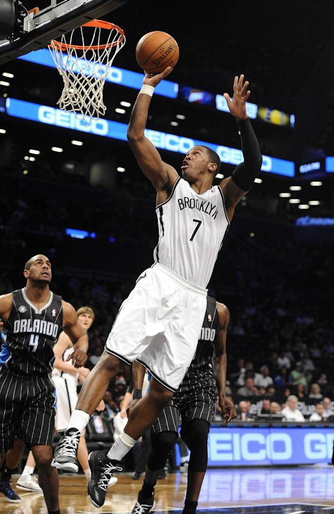 Orlando Magic' Arron Afflalo (4) watches Brooklyn Nets' Joe Johnson (7) drive the ball to the basket in the first half of an NBA basketball game Sunday, April 13, 2014, in New York