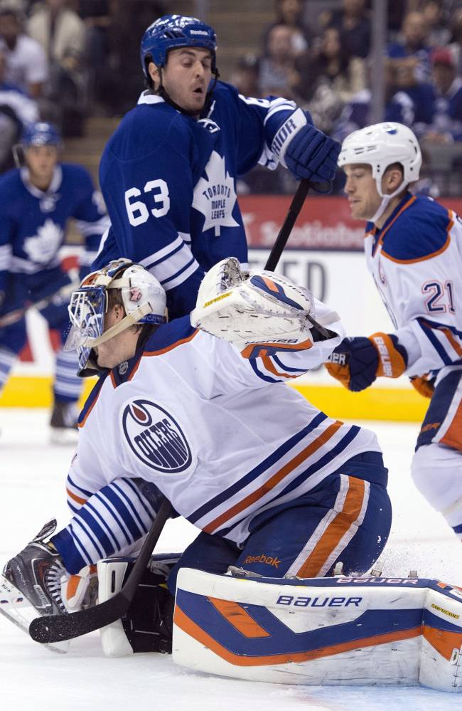 Toronto Maple Leafs Dave Bolland (63) picks up a goaltender interference call as he runs into Edmonton Oilers goaltender Devan Dubnyk during the second period of an NHL hockey game, Saturday, Oct. 12, 2013 in Toronto