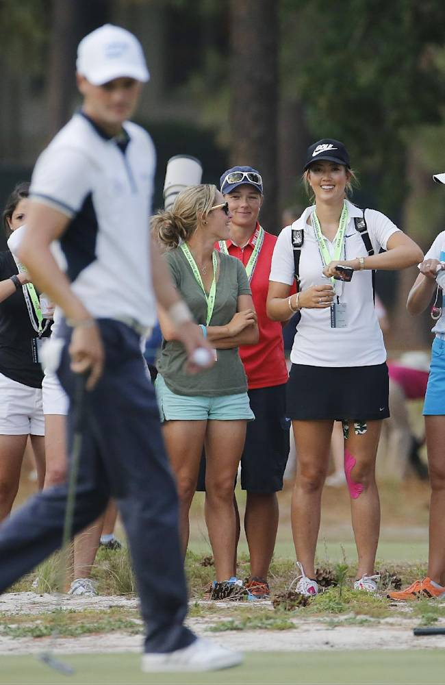 Martin Kaymer, of Germany, lines up his putt as a group of LPGA plays watch from the fairway on the 17th hole during the final round of the U.S. Open golf tournament in Pinehurst, N.C., Sunday, June 15, 2014. he women's U.S. Open golf tournament starts Thursday on the same course