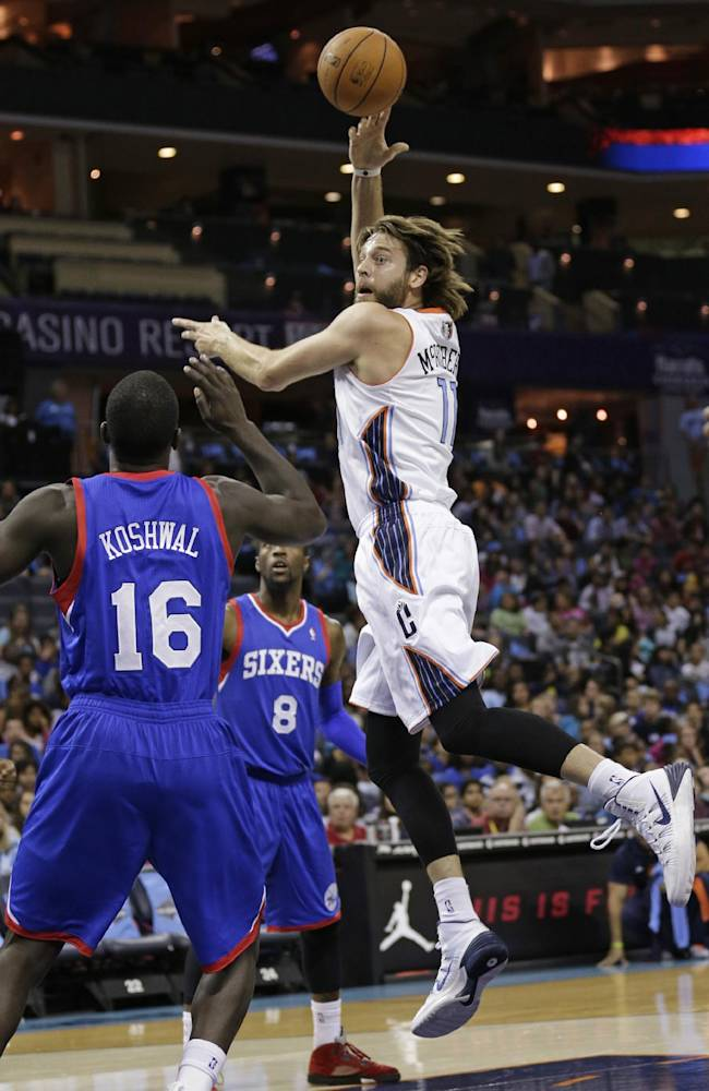 Charlotte Bobcats' Josh McRoberts, right, passes the ball as Philadelphia 76ers' Mac Koshwal, left, and Tony Wroten (8) defend during the first half of a preseason NBA basketball game in Charlotte, N.C., Thursday, Oct. 17, 2013