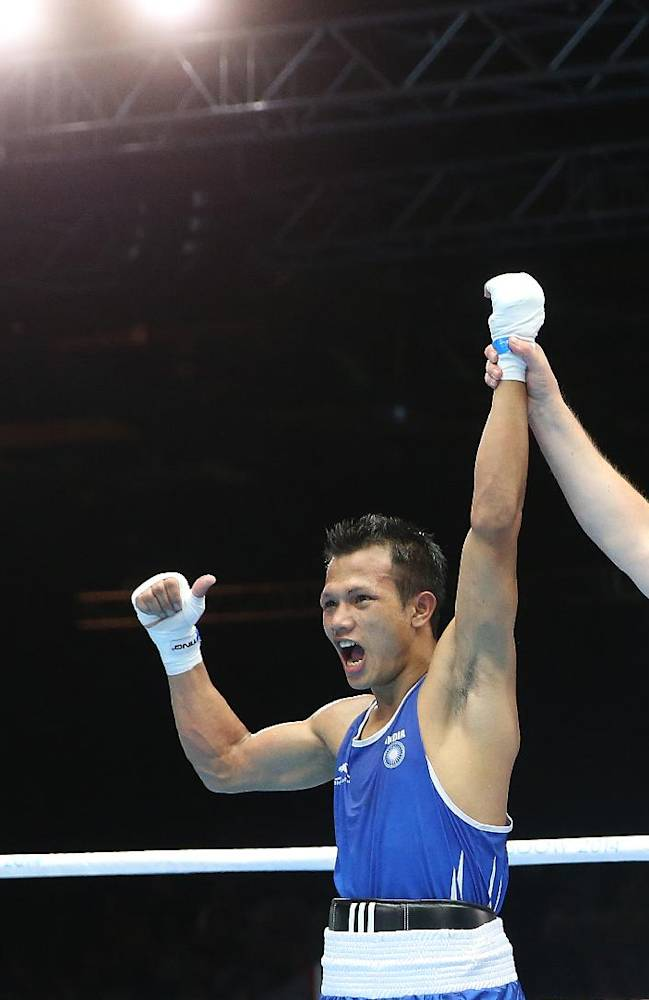 India's Devendro Laishram celebrates defeating Sri Lanka's Madushan Gamage in the Men's light flyweight preliminaries bout at the Commonwealth Games Glasgow 2014, Glasgow, Scotland, Monday July 28, 2014