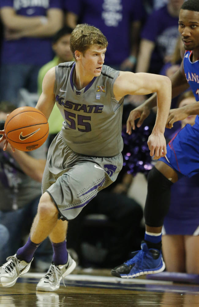 Kansas State guard Will Spradling (55) handles the ball while covered by Kansas guard Wayne Selden, Jr. (1) during the second half of an NCAA college basketball game in Manhattan, Kan., Monday, Feb. 10, 2014. Kansas State defeated Kansas 85-82 in overtime