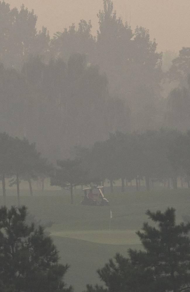 A buggy drives through the court on a hazy day after the second round of the Reignwood LPGA Classic golf tournament at Pine Valley Golf Club on the outskirts of Beijing, China, Friday, Oct. 4, 2013