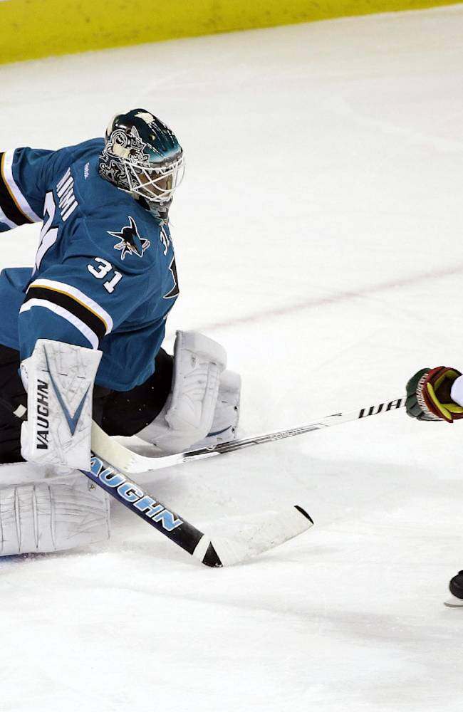 Minnesota Wild's Matt Cooke (24) scores past San Jose Sharks goalie Antti Niemi, of Finland, during the first period of an NHL hockey game on Saturday, Jan. 25, 2014, in San Jose, Calif