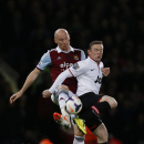 West Ham United's James Collins, left, competes with Manchester United's Wayne Rooney during their English Premier League soccer match at Upton Park, London, Saturday, March 22, 2014