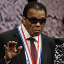 Retired boxing champion Muhammad Ali waves after receiving the Liberty Medal during a ceremony at the National Constitution Center, Thursday, Sept. 13, 2012, in Philadelphia. The honor is given annually to an individual who displays courage and conviction while striving to secure liberty for people worldwide. (AP Photo/Matt Rourke)