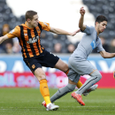 Hull City's Michael Dawson, left, and Newcastle United's Ayoze Perez battle for the ball during their English Premier League match at the KC Stadium, Hull England Saturday Jan. 31, 2015