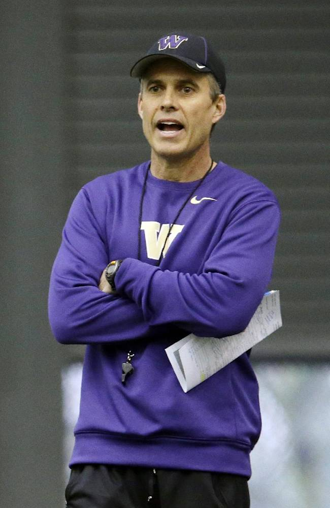 New Washington head football coach Chris Petersen calls to his team on the first day of spring NCAA college football practice, Tuesday, March 4, 2014, in Seattle
