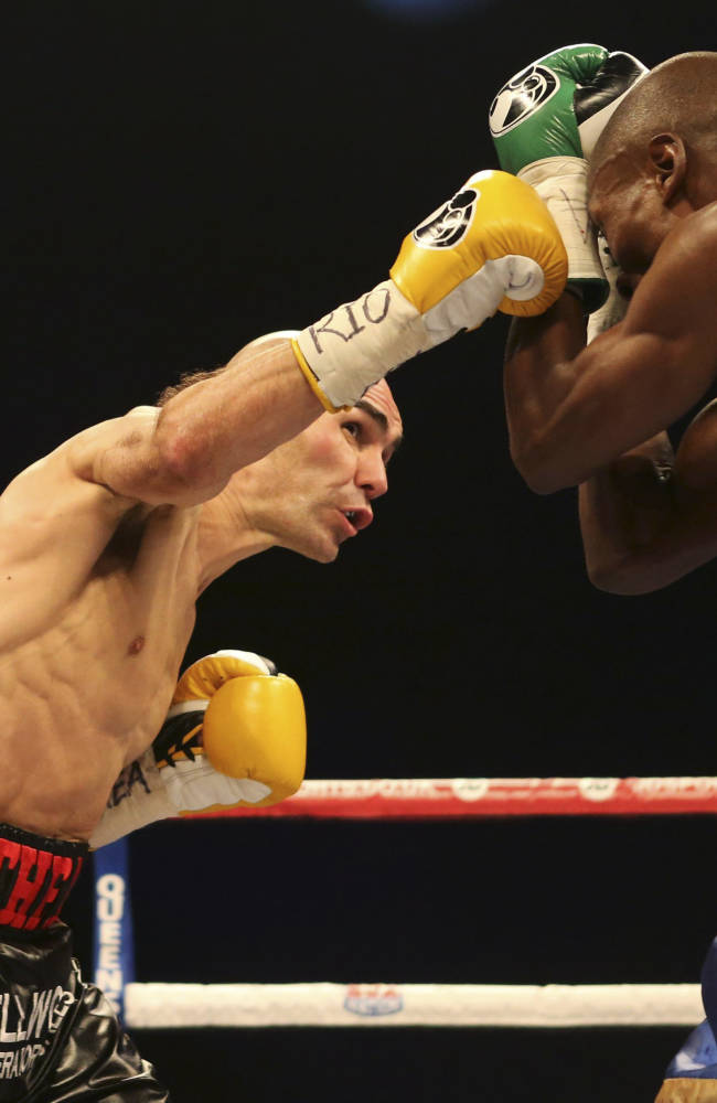 Britain's Stuart Hall, left, punches South Africa's Vusi Malinga during their IBF bantamweight title fight at the First Direct Arena, in Leeds, England, Saturday Dec. 21, 2013. Hall claimed the vacant IBF bantamweight title on Sunday after a points win over Malinga