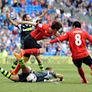Cardiff City's Kim Bo-Kyung, center left, brings down Stoke City's Peter Odemwingie, below, resulting in a penalty during their English Premier League soccer match at the Cardiff City Stadium, Cardiff, Wales, Saturday, April 19, 2014