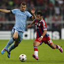 Manchester City's Edin Dzeko, left, and Bayern's Juan Bernat, right, challenge for the ball during the Champions League Group E soccer match between FC Bayern Munich and Manchester City at Allianz Arena in Munich, southern Germany, Wednesday Sept. 17, 201