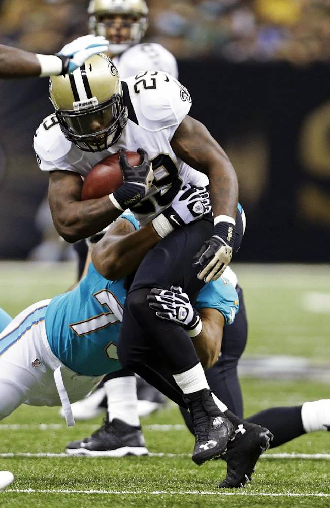 New Orleans Saints running back Khiry Robinson (29) rushes as Miami Dolphins defensive end Derrick Shelby (79) attempts to tackle in the first half of an NFL football game in New Orleans, Monday, Sept. 30, 2013