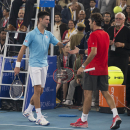 Micromax Indian Aces player Roger Federer, right, and Musafir.com UAE Royals Novak Djokovic greet each other after their game during International Premier Tennis League, in New Delhi, India, Monday, Dec. 8, 2014. (AP Photo/Manish Swarup)