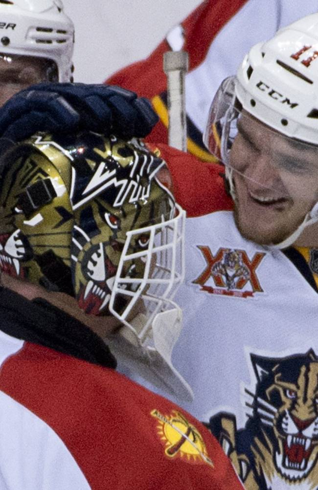 Florida Panthers center Jonathan Huberdeau (11) celebrates with teammate Tim Thomas following the shootout against the Vancouver Canucks in NHL action in Vancouver, British Columbia, Tuesday, Nov. 19, 2013