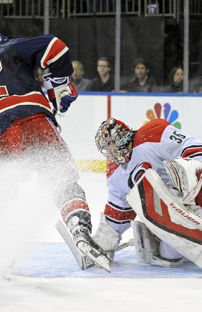 New York Rangers' Carl Hagelin, left, scores a goal past Carolina Hurricanes goaltender Justin Peters during the second period of an NHL hockey game Saturday, Nov. 2, 2013, at Madison Square Garden in New York