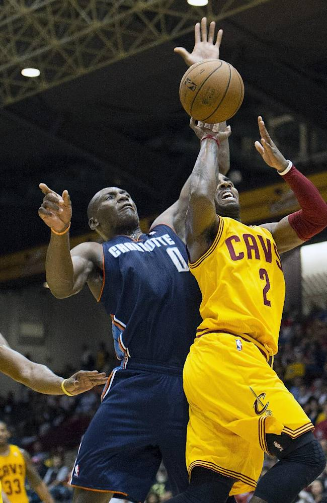 CORRECTS SPELLING OF BIYOMBO'S FIRST NAME TO BISMACK, INSTEAD OF BISMARK - Cleveland cavaliers guard Kyrie Irving, right, is fouled by Charlotte Bobcats defender Bismack Biyombo during the first quarter of an NBA preseason basketball game in Canton, Ohio on Tuesday, Oct. 15, 2013