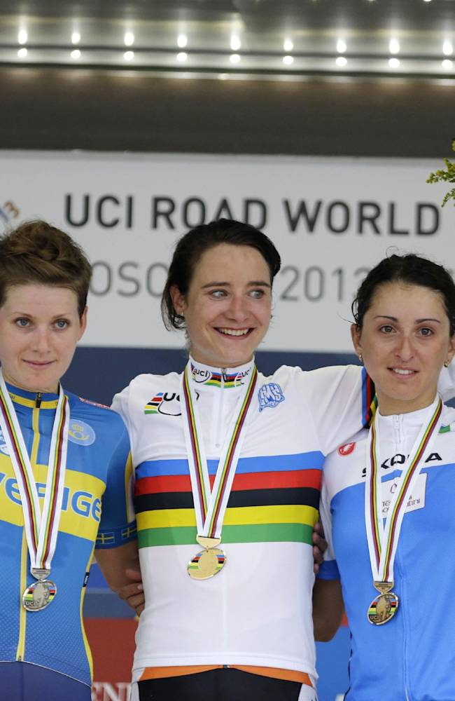 Gold medal's winner Dutch cyclist Marianne Vos, center, is flanked by silver medalist Sweden's Emma Johansson, left, and bronze medalist Italy's Rossella Ratto, on the podium of the women's elite road race event, at the road cycling world championships, in Florence, Italy, Saturday, Sept. 28, 2013