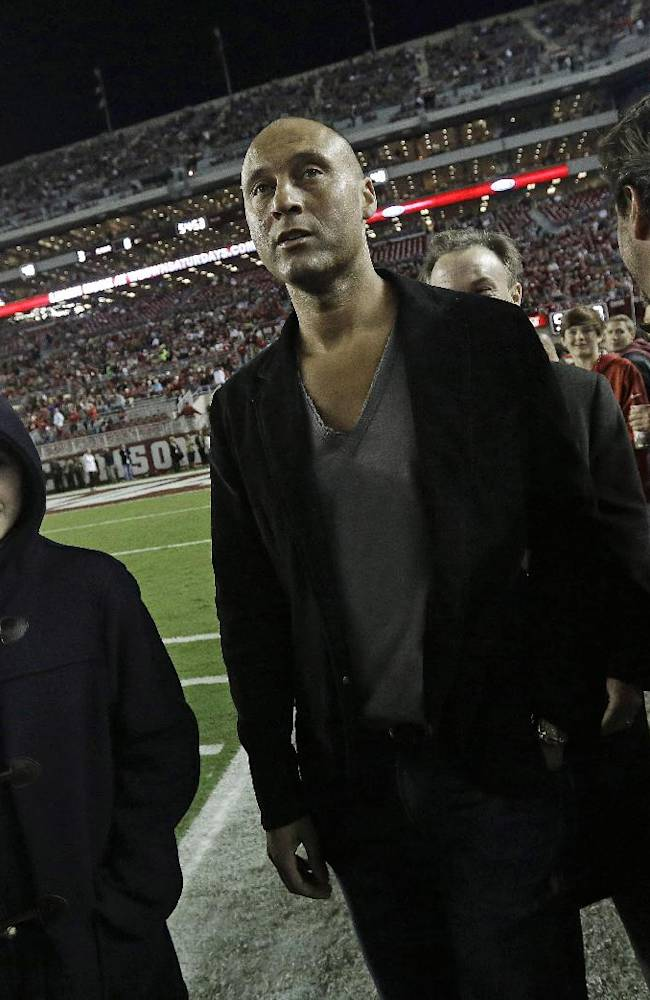 New York Yankee's Derek Jeter, center, walks on the field before the first half of an NCAA college football game between Alabama and LSU, Saturday, Nov. 9, 2013, in Tuscaloosa, Ala