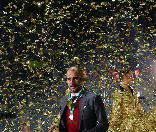 In this picture taken May 17, 2014, Bayern Munich coach,  Pep Guardiola , enjoys the celebrations in a confetti shower after his team won the German soccer cup final against Borussia Dortmund in Berlin