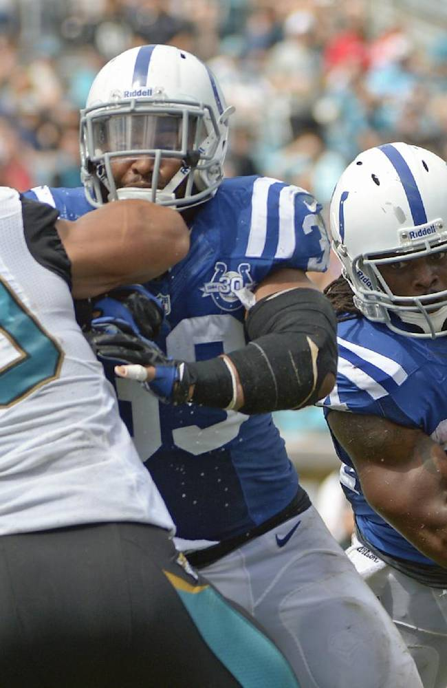 Indianapolis Colts running back Trent Richardson, right, gets a block from fullback Stanley Havili, center, as he runs past Jacksonville Jaguars outside linebacker Russell Allen (50) for a 1-yard touchdown during the first half of an NFL football game in Jacksonville, Fla., Sunday, Sept. 29, 2013