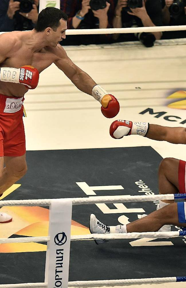 World boxing champion Wladimir Klitschko of Ukraine, left, knocks down Samoan-born Australian challenger Alex Leapai during their IBF, IBO, WBO and WBA heavyweight title bout in Oberhausen, Germany, Saturday, April 26, 2014. Klitschko won the fight by technical knock out in the fifth round