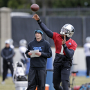 Carolina Panthers quarterback Cam Newton, right, prepares to throw a pass as quarterbacks coach Ken Dorsey, left, looks on during an NFL football practice in Charlotte, N.C., Thursday, Dec. 18, 2014. (AP Photo/Chuck Burton)