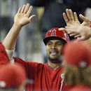 Los Angeles Angels' Albert Pujols celebrates in the dugout after scoring on a single by David Freese against the Los Angeles Dodgers during the third inning of an exhibition baseball game in Los Angeles, Friday, March 28, 2014 The Associated Press