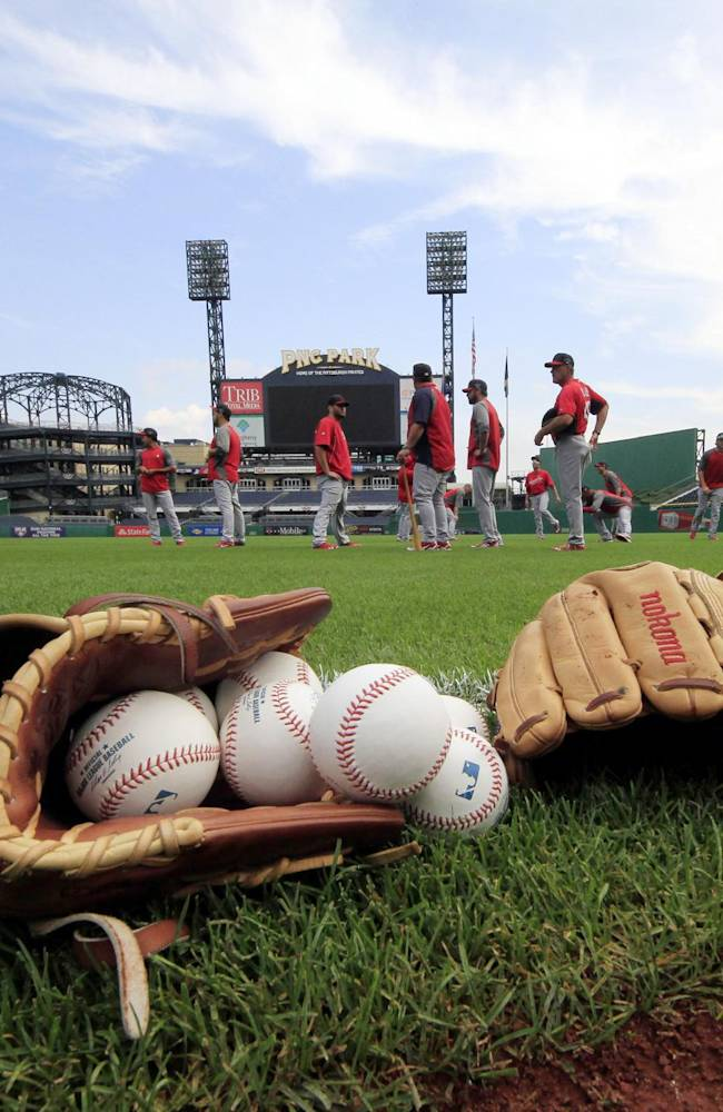 St. Louis Cardinals starting pitcher Adam Wainwright, left, walks to the outfield during a baseball workout at PNC Park Saturday, Oct. 5, 2013, in Pittsburgh. The Cardinals are scheduled the Pittsburgh Pirates in Game 3 of the National League division series on Sunday