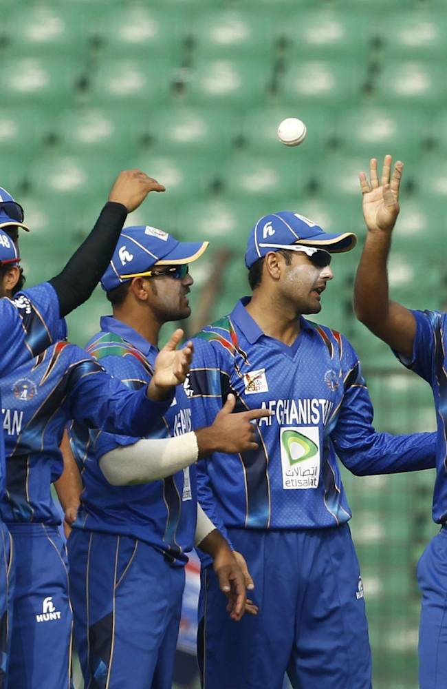 Afghanistan's players celebrate the wicket of Pakistan's Mohammad Hafeez during the Asia Cup one-day international cricket tournament in Fatullah, near Dhaka, Bangladesh, Thursday, Feb. 27, 2014
