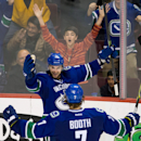 Vancouver Canucks' Brad Richardson, top, and David Booth celebrate Richardson's goal against the Los Angeles Kings during the third period of an NHL hockey game Saturday, April 5, 2014, in Vancouver, British Columbia. Vancouver won 2-1 The Associated Pres